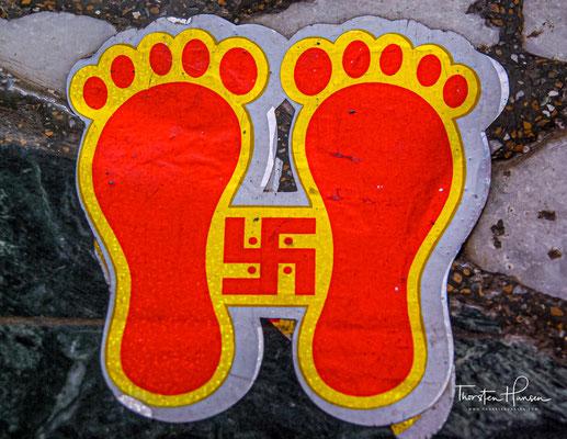 Eine Swastika ist ein Kreuz mit vier Schenkeln. Hindus und Buddhisten verehren es als Sonnenrad und als Symbol des Glücks.