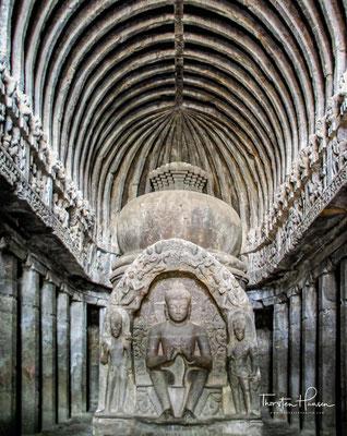 Ellora – Chaitya 10. Die Hände der großen – in europäischer Sitzhaltung gezeigten – Buddhafigur zeigen den Lehrgestus (dharmachakramudra).