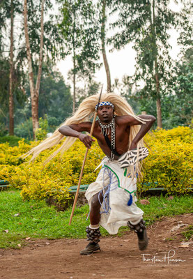 ... eine mit den Händen über dem Kopf von oben offene ovale Form zu tanzen, um die Form der Hörner von 'Inyambo', den langhörnigen Kühen zu symbolisieren ).