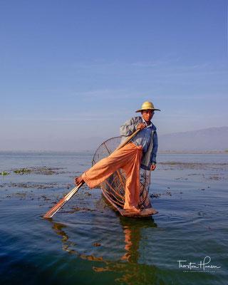 Die Ruderer vom Volk der Intha stehen mit geradezu artistischem Geschick mit einem Bein auf der kleinen Plattform am Heck ihres Holzbootes.