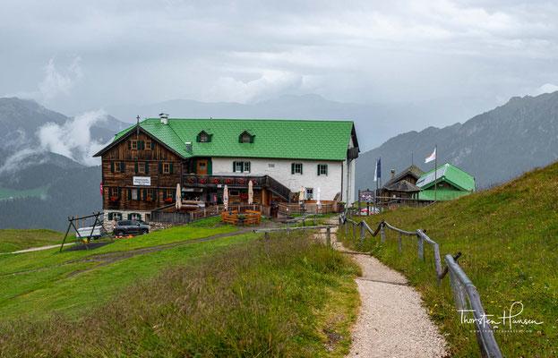 """Die Schlüterhütte wurde 1898 erbaut. Sie liegt eingebettet in Almwiesen auf 2306 m, zwischen Geislergruppe und Peitlerkofel, im Naturpark Puez-Geisler, einem Teil des Weltnaturerbe """"Dolomiten""""."""