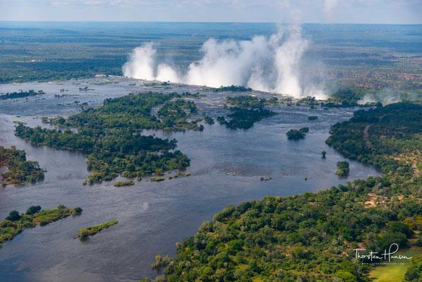 """schießen bis zu 10.000 m³/s Wasser über den Nordrand der Schlucht in die Tiefe, jedoch wird der Wasserfall auch in den meisten anderen Monaten des Jahres dem Titel """"größter Wasservorhang der Erde"""" gerecht."""