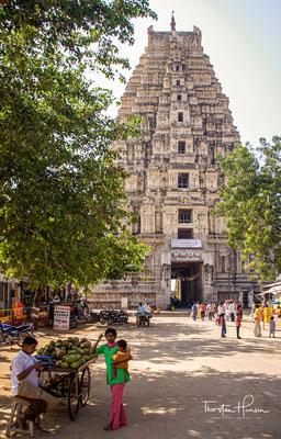 42 Meter hoher Gopuram des Virupaksha-Tempels, erbaut um 1440. Der den Ort überragende, 2017 renovierte, Virupaksha-Tempel und die zuführende Hampi-Bazaar-Straße ist von Einheimischen, Pilgern und Händlern aus anderen Bundesstaaten belebt.