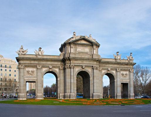 """Die Puerta de Alcalá (""""Alcalá-Tor"""") ist ein Monument in Madrid (Spanien), welches sich im Zentrum der Stadt an der Plaza de la Independencia (""""Unabhängigkeitsplatz"""") befindet."""