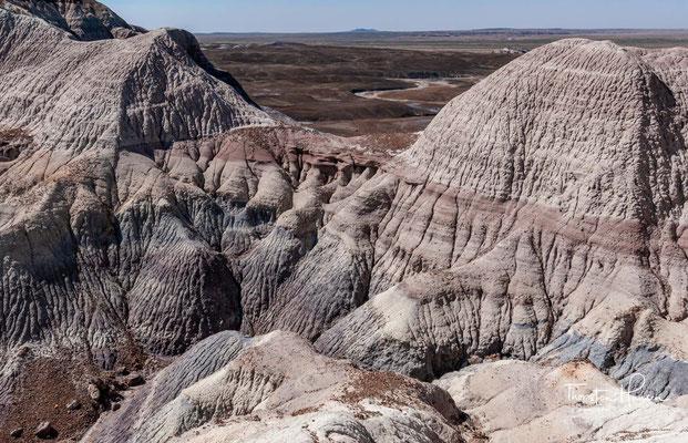 """Innerhalb des Parks lässt sich das Fortschreiten der Erosion gut beobachten. Während an den """"Tepees"""" die oberste Tonschicht schon fast abgetragen ist, so ist im höher liegenden Gebiet der """"Blue Mesa"""" bislang nur diese sichtbar."""