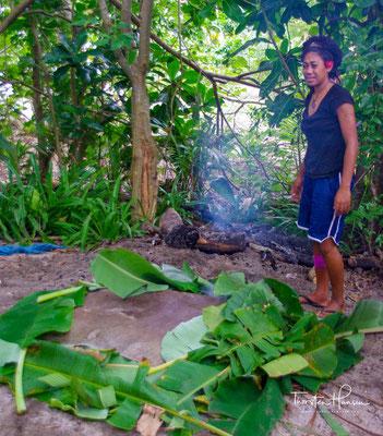 Das Essen für den Erdofen wird sitzend zubereitet und dann in Alufolie und Palmenblätter verpackt. Sind die Steine heiß genug, wird das Feuer gelöscht und die Steine zusammen mit dem Essen in den Erdofen gelegt