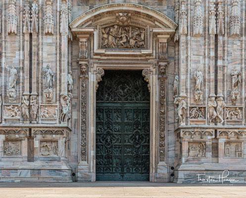Die Bronzetüren des Hauptportals von Lodovico Poliaghi zeigt die Sieben Freuden Mariae gegenüber einer Verbildlichung ihrer Sieben Schmerzen.