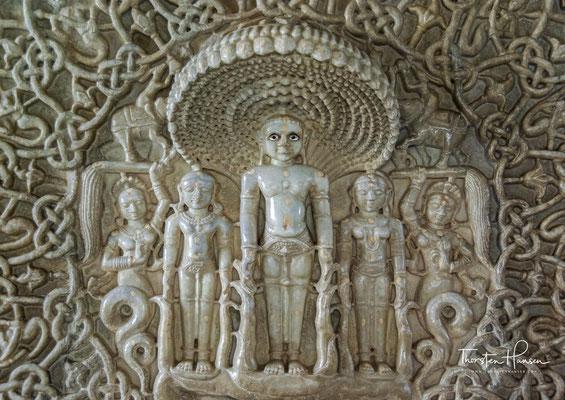 ...als auch einige wenige Zierstücke wie die kleine Figur des von Dienerinnen begleiteten und von einer Schlangenhaube beschützten Tirthankaras Parshvanata an der Cella, die von einem äußerst kunstvollen Flechtwerk gerahmt wird,...
