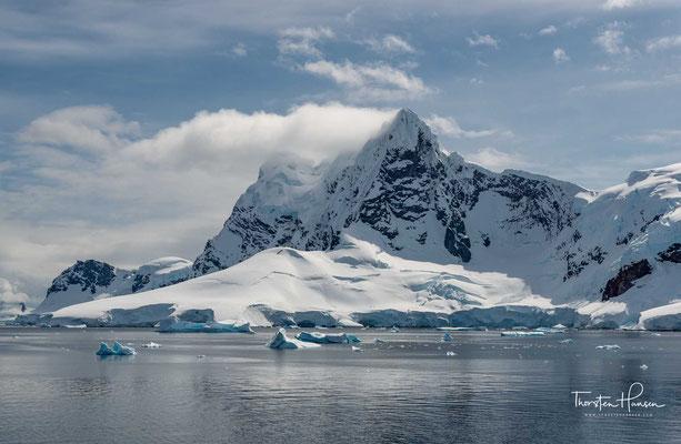 Die Gletscher und Klippen spiegeln sich in den stillen Wasserflächen am südlichen Ende des Kanals. Wenn Eisberge die Weiterfahrt nach Süden blockieren, sind die Kreuzfahrtschiffe gezwungen umzukehren und die Booth-Insel zu umrunden, um die Petermann-Insel