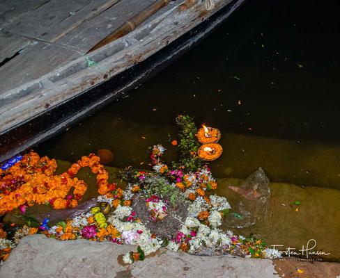Viele Boote setzen zum anderen Flussufer des heiligen Flusses über. uns viele andere Menschen machen Yoga.