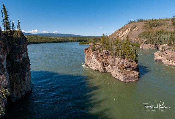 """Die Five Finger Rapids sind eine Felsformation im Yukon River im kanadischen Territorium Yukon, 20 km flussabwärts von Carmacks am Klondike Highway. Vier Felssäulen aus Basalt teilten den Fluss in fünf Stromschnellen, die """"Finger""""."""