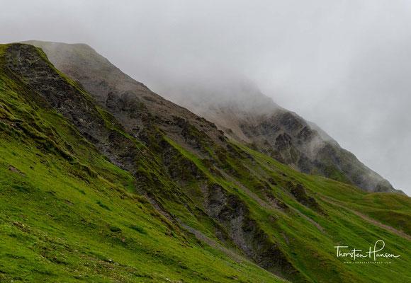 Allerdings blühen überall Bergblumen in herrlichen Farben. Der Boden ist so karg, dass Viehwirtschaft hier oben nicht lohnt. So hat die Landschaft noch einen ganz ursprünglichen Charakter.