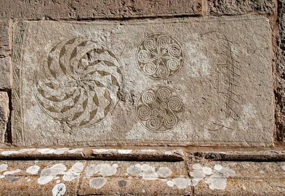 Einer der herausragenden Bildsteine mit drei Wirbelradmotiven und der Darstellung eines Ruderbootes ist westlich des südwestlichen Portals der Kirche waagerecht eingemauert. Seine Länge beträgt 1,88 m. Er wird in die Zeit zw. 400 und 600 n. Chr. datiert