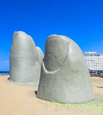 Es stellt die Finger einer riesigen Hand dar, die durch den Sand ragen.