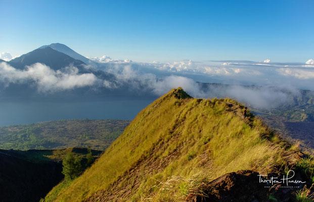 Die Abhänge sind bedeckt von dunklen Lavafeldern, die sich weit in die gewaltige Caldera hinunterziehen. Immerhin ist der Mt. Batur der aktivste aller Vulkane auf Bali.