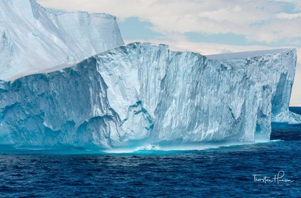 Im Allgemeinen sind Eisberge weiß. Die weiße Farbe wird durch die Reflexion des Lichtes an der im Eis eingeschlossenen Luft hervorgerufen