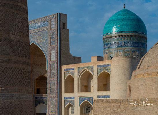 Das Minarett steht an der Südseite des Platzes zwischen der Kalon-Moschee (vollendet 1514) und der Mir-Arab-Madrasa (vollendet 1536/37), die einander im Kosch-Prinzip gegenübergestellt sind.