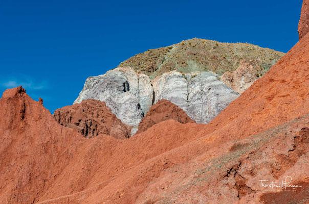 Erdfarben, Rot, Beige, Grün, Weiß, Gelb, kombiniert mit weißem Salz und blauem Himmel.