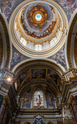 Hinter der schlichten doppeltürmigen Fassade mit korinthischen Säulen verbirgt sich ein prächtiger barocker Innenraum mit vielen Wand- und Deckenfresken.