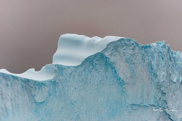 Tiefblau schimmert ein Eisberg nur, wenn er sehr wenige Luftbläschen enthält. Diese Tatsache hat mit den Eigenschaften von luftarmem Eis zu tun.