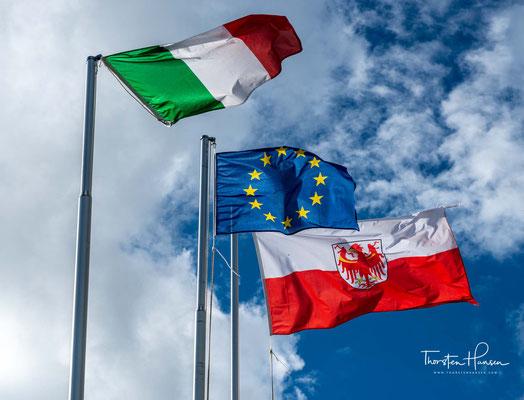 Die italienische, europäische und Südtiroler Fahne in der Nähe der Puez-Hütte