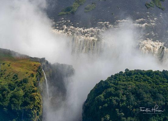 Schrägluftbild der Victoriafälle mit Blick nach Norden, den breiten Oberlauf des Sambesi hinauf; ganz unten mittig der Boiling Pot, links daneben die Victoria Falls Bridge