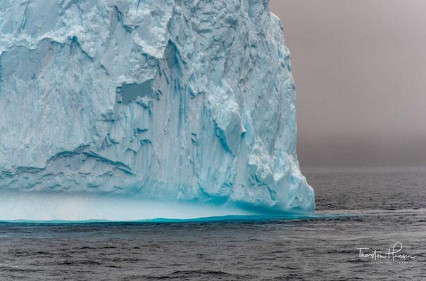Hinter einer ein Meter dicken klaren Eisschicht könnte man die Sonne noch deutlich erkennen. Bei der Erklärung, warum Eisberge blau sind, kommt es im Kern auf die farbabhängige Schwächung des Lichts an.