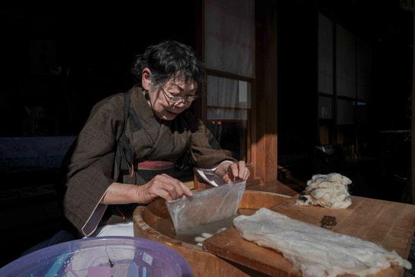 真綿かけ :   重曹でゆでた繭を指で広げ、5−6枚を重ねて袋状の綿を作る。