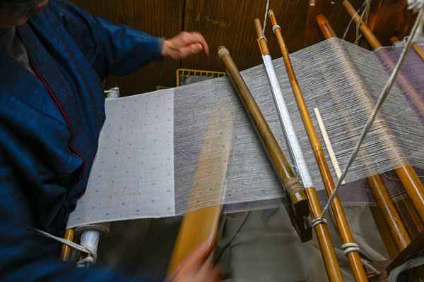 地機織り:  杼(ひ)うち 筬(おさ)で横糸を打ち込んだのち、杼でさらに打ち込む。  この杼は樫でできた重さ約600グラム、長さ約55センチのもので、この地機織の特徴である。
