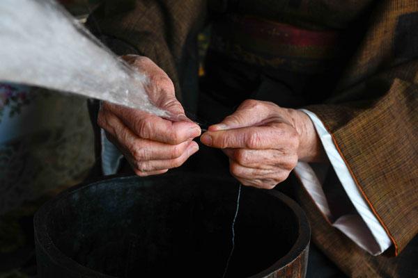 手紡ぎ:    真綿から糸を引き出し唾をつけながら紡いでゆく。 縦糸横糸など用途に応じて太さを変え均等に紡ぐ技術は三年以上の修行を要するという。