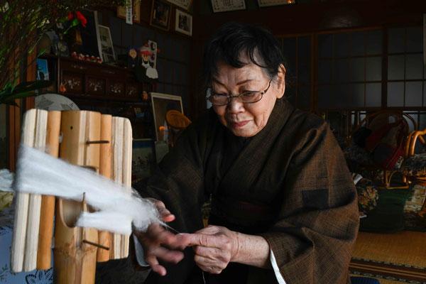 糸紡ぎ :   ツクシという道具に真綿を巻き、手で紡いで桶に入れてゆく。 縒りを全く掛けないのが特徴であり、一反分をを作るのに二−三ヶ月が必要という。