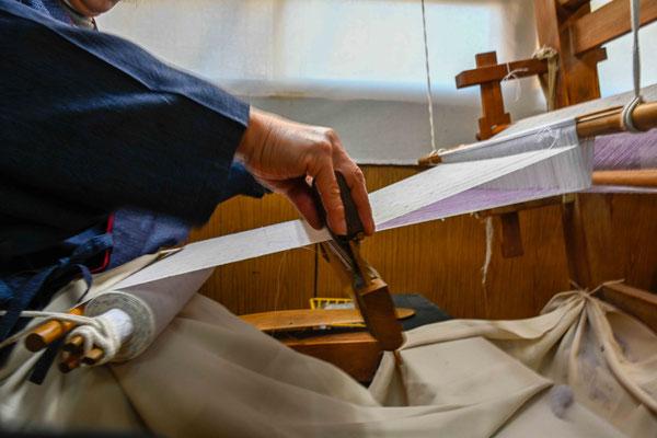 地機織り:   筬(おさ)うち 地機の一つの特徴は、機に張る縦糸を腰当てに結び、腰の力で張り具合を調節するものである。 これによりつむぎ糸の弾力と柔らかさが最大に生かされている。  前出の杼を使い通した横糸をまず筬で打ち込む。