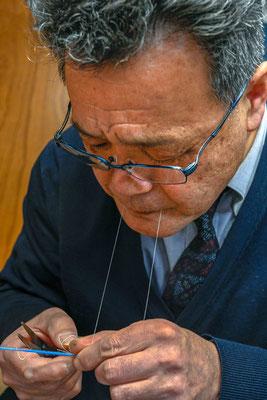 かすり模様を綿糸で括る:    図面から墨付けをした場所に糸を括ってゆく。  伝統工芸士の外山正美さん(写真)によると現在作業中の作品は160亀甲紋で完成には、時間を見ながらやっているので2年以上かかる予定だそうである。