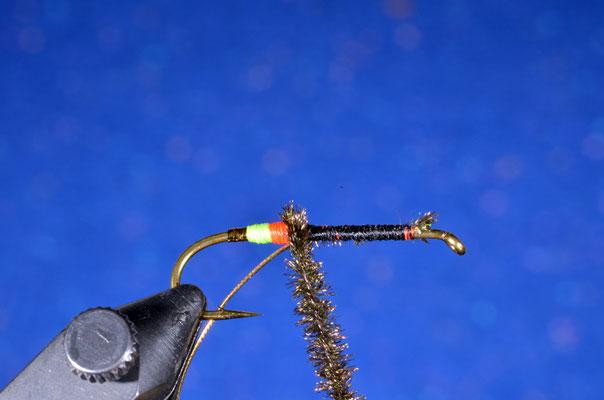 """Per ottenere un corpo uniforme e particolarmente robusto, si avvolge il ciuffo di herl di pavone attorno al filo di montaggio: si otterrà un """"cordino"""" di pavone molto resistente"""