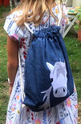 Schulanfängerin trägt stolz den Beutebeutel (Rucksack) mit Pferd- Applikation.