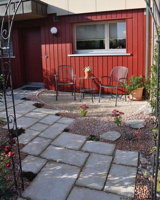 ...in einen kleinen roten Garten mit Sitzecke.