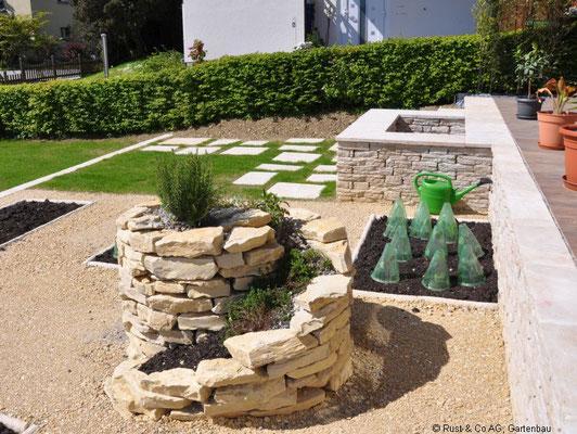 ...einen Garten mit Pflanzbeeten und einer Kräuterspirale...
