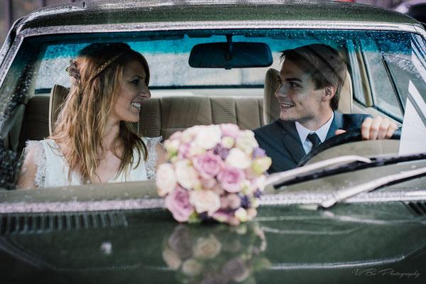 Brautpaar im Hochzeitsauto bei Regen.