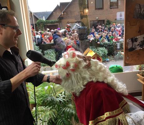 Sinterklaas in de kapsalon met uitzicht op straat.