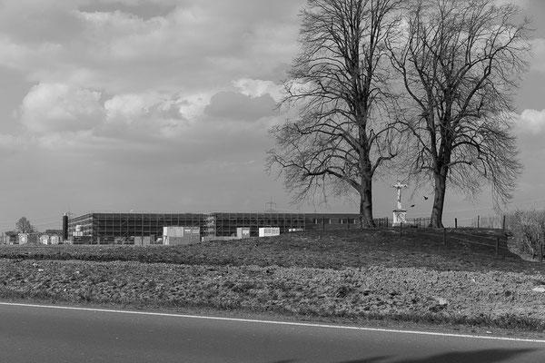 Blick auf entstehende Verwaltungsbauten am Hansa-BusinessPark. Im Vordergrund ein Wegkreuz.