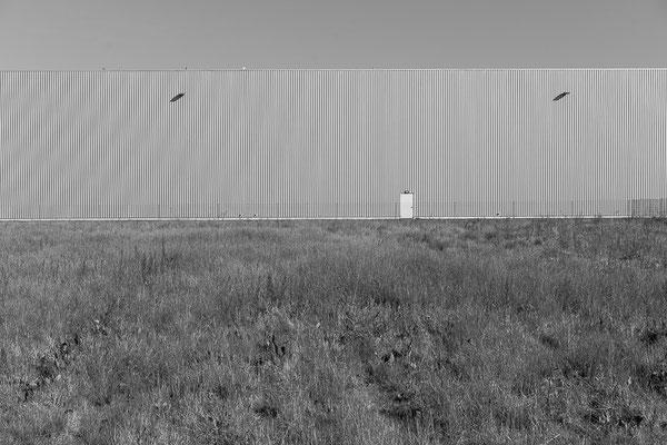 Brachfläche und Fassade einer Industriehalle