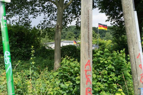 Blick über eine Kleingartenanlage bei Münster-Nord. Im Hintergrund ist eine Deutschlandfahne zu sehen. Im Vordergrund Graffitis: ACAB und 1906