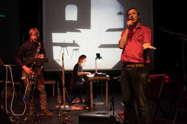 Liedermacher Broeder Dieleman vor einer Schattenprojektion von Lies van Gasse