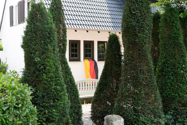 Schwarz-rot-goldene Deutschlandfahne an dem Fenster eines Einfamilienhauses.