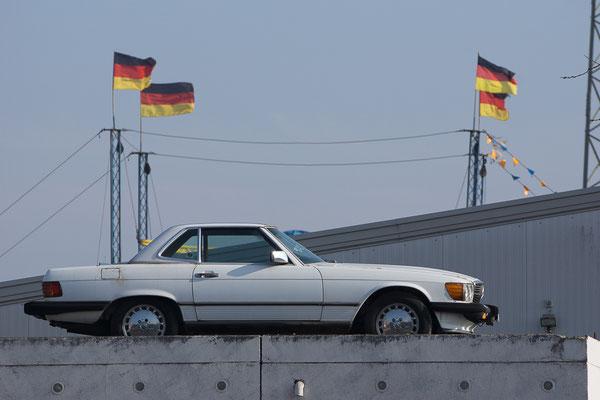 Mercedes Sportwagen mit an Masten wehenden Deutschlandfahnen im Hintergrund.