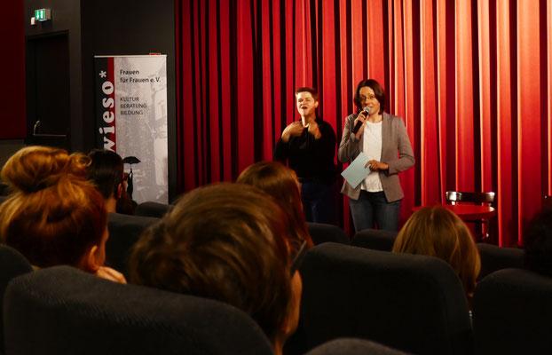 Susanne Seifert (Kuratorin des Filmprogamms) begrüßt die Gäste unterstützt durch Vigevo - Das Netzwerk für Gebärdensprachdienstleistungen.