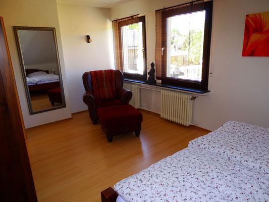 Schlafzimmer mit gemütlichem Sessel und Leselampe