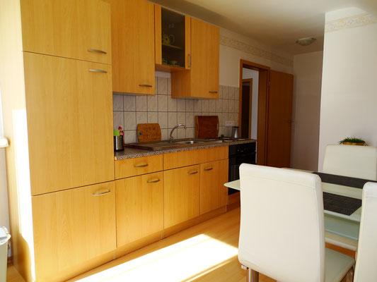 Voll eingerichtete Küche mit Kühlschrank inklusive Gefrierfach und E-Herd mit Backofen
