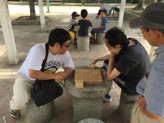 将棋を打つスタッフ
