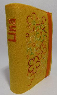 Stickmotiv Blumen in grün-orange auf gelbem Filz, Schriftart AR Cena